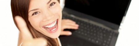 Laptop woman happy giving thumbs up success sign sitting at computer PC with excited face expression