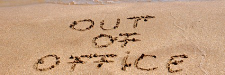 Out of office text written on the beach sand